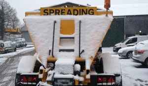 A Surrey gritter covered in snow after treating roads winter weather
