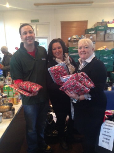 Adult Social Workers Cathy Heath and Kim Kurani deliver Christmas presents to Food Bank Manager Jonathan Lees.